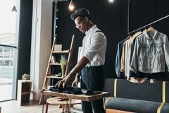 Searching for fresh ideas. Serious young man arranging menswear. While standing in the showroom Stock Photos