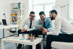 Searching for fresh ideas together. Group of young modern men in formalwear working using digital tablet while sitting in the office royalty free stock photo