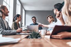 Searching for fresh ideas together. Group of young modern people in smart casual wear discussing business while working in the creative office stock photography