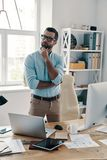Searching for fresh ideas. Young modern businessman keeping hand on chin and looking away while working in the office royalty free stock photo
