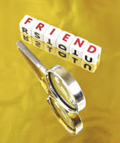 Searching for a friend. Text ' friend ' in red uppercase letters on small white cubes placed on a gold background with a hand magnifier indicating the search Stock Photo