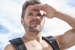 Searching hiker. Closeup of intense expression and concentration of bearded male Caucasian hiker shielding his eyes from sun as he searches Royalty Free Stock Photography
