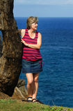 Searching the Horizon. Woman stands on cliffs edge searching the horizon.  She is wearing a denim skirt and colorful top Royalty Free Stock Images