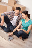 Searching a house moving company. Top view of beautiful young couple sitting on the floor and working on laptop while cardboard boxes laying on the background stock images