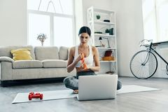 Searching how to do exercise. Beautiful young woman in sports clothing using laptop while exercising at home royalty free stock photography