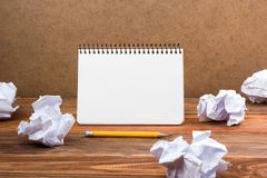 Searching an idea, motivation, result, dwaing scetches. White blank notepad book at office worplace crampled paper notes. On wooden grunge background. Copy stock image