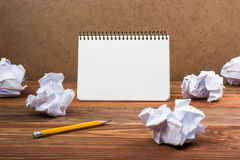 Searching an idea, motivation, result, dwaing scetches. White blank notepad book at office worplace crampled paper notes. On wooden grunge background. Copy royalty free stock photography