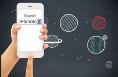 Searching information about planets. Child hand with holding a smart phone and searching information of planets with homepage and blackboard with drawing planets stock image