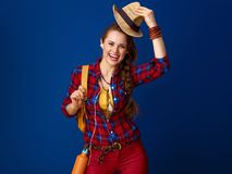 Tourist woman with headphones listening to music and rising hat Royalty Free Stock Images