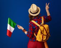 Adventure woman hiker with flag of Italy showing victory. Searching for inspiring places. Seen from behind adventure woman hiker with backpack and the flag of Royalty Free Stock Photography