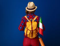 Woman hiker isolated on blue background with flag of Italy. Searching for inspiring places. Seen from behind young woman hiker with backpack with the flag of Stock Photography
