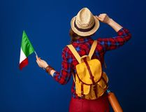 Young woman hiker isolated on blue with flag of Italy. Searching for inspiring places. Seen from behind young woman hiker with backpack and the flag of Italy Royalty Free Stock Photos
