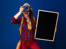 Tourist woman with blackboard and DSLR camera taking photo Stock Photography