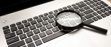 Searching On Internet Concept, Magnifier On Computer Keyboard Royalty Free Stock Photos