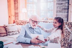 Preschooler explaining elderly man how searching the Internet stock photo