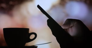 Searching internet smart phone while drinking coffee tea at night stock footage