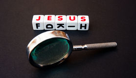 Searching for Jesus. Text ' Jesus ' in uppercase red letters inscribed on white cubes alongside a hand magnifier indicating the search, dark background Royalty Free Stock Image