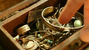 Searching in a Jewelry Box. Close up of a hand searching in a glowing treasure chest stock footage
