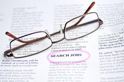 Searching job. With newspaper and glasses stock images