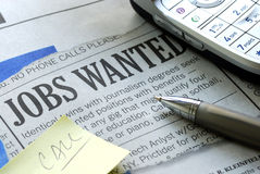 Searching for a job from a newspaper royalty free stock photography