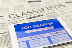 Searching job with tablet and classifieds ads Royalty Free Stock Photography