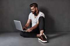Searching for the latest tunes. Handsome young man wearing headphones around his neck and using computer while sitting on the floor against grey background Stock Images