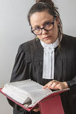 Searching the law. Thirty something brunette woman wearing a canadian lawyer toga with a red criminal law book in hand looking over her glasses Stock Images