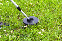 Searching a lawn with a metal detector Stock Images