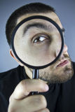 Searching Man. Young man searching withy magnifying glass royalty free stock photography
