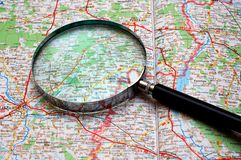 Searching on a map. With magnifying glass Stock Photos