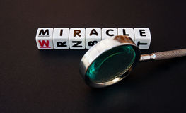 Searching for a miracle. Text ' miracle ' in black uppercase letters on small white cubes together with hand magnifier, dark background Royalty Free Stock Image