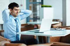 Searching Mistake in Calculations. Tired handsome financial manager putting hands on nape and searching mistake in his calculations on laptop, waist-up portrait Royalty Free Stock Photo