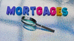 Searching for mortgages. Text 'mortgages' in colorful uppercase letters with hand held magnifier along side to indicate the search, reflective background Stock Images