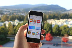 Searching new app on iPhone with nature background. Coquitlam BC Canada - October 06, 2014 : Searching new app on iPhone with nature background, IPhone is one of Royalty Free Stock Images