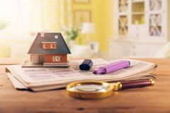 Searching new house in newspaper real estate classifieds. Scale model on the table royalty free stock photos