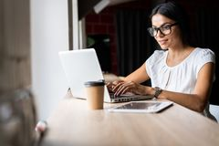 Searching for new solution. Pensive young beautiful businesswoman in glasses working on laptop while sitting at her Royalty Free Stock Photo