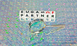 Searching for a partner. Text 'partner' in black uppercase letters inscribed on small white cubes with hand held magnifier in front to symbolize searching Royalty Free Stock Photography