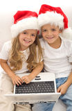 Searching for the perfect christmas gift online. Kids with laptops and santa hats stock images
