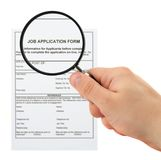 Searching for personnel. Concept of searching for personnel - hand with magnifying glass and job application form royalty free stock photography
