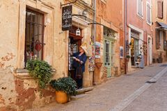 Searching for postcards in a village street. ROUSSILLON, FRANCE, April 6, 2018 : Luberon region is a favourite destination for French, British and American Stock Images