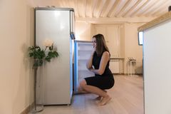 Searching the refrigerator for something to eat. Young woman with opened fridge searching and taking out some food to prepare. What to eat and cook royalty free stock images