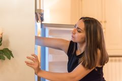 Searching the refrigerator for something to eat. Young woman with opened fridge searching and taking out some food to prepare. What to eat and cook royalty free stock photo
