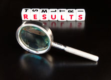 Searching for results. Text ' results ' in red uppercase letters inscribed on small white cubes placed beside a hand magnifier , dark background Stock Photography