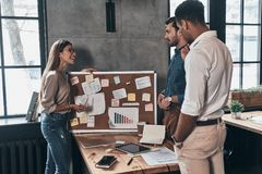 Searching for right decision. Group of young business people usi Royalty Free Stock Image