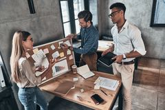 Searching for right decision. Top view of young business people. Using blackboard with adhesive notes while working in the office Stock Photos