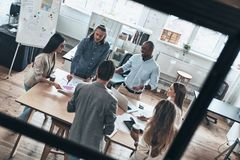 Searching for right decision. Top view of young modern people in. Smart casual wear discussing business while standing behind the glass wall in the board room Royalty Free Stock Images