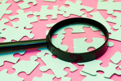 Searching For The Right Piece. Black magnifying glass searching for the right piece of the puzzle Royalty Free Stock Photo