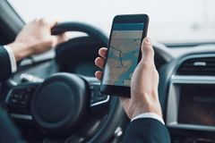 Searching for the shortest way. Close up of young man using smart phone to check the map while driving a car stock photos