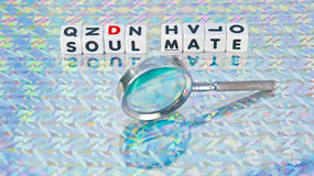 Searching for a soul mate. Text 'soul mate' inscribed in black uppercase letters on small white cubes  with nearby hand held magnifier, patterned background Stock Photos
