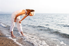 Searching or stretching. Woman at the beach, maybe searching for shells royalty free stock photos